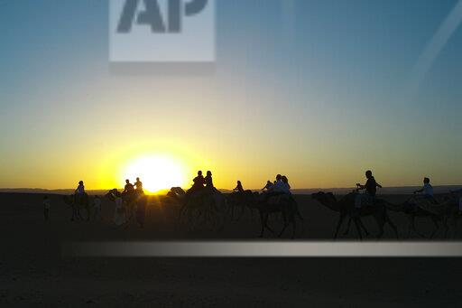 Morocco, people on camels at sunset