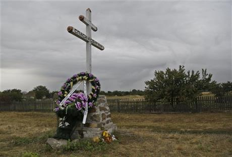 A commemorative wreath is laid at the foot of a cross, near the wreckage of Malaysia Airlines Flight 17 plane seen outside the village of Hrabove, eastern Ukraine, Tuesday, Sept. 9, 2014.