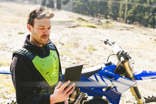 Portrait of motocross driver looking at tablet