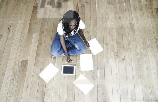 Woman sitting on the floor with digital tablet and blank sheets of paper