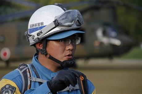A Nagano Prefectural police officer covered by volcanic ash talks to the media after coming back from his mission to recover bodies still near the summit as Mount Ontake continues to erupt in Otaki in Nagano Prefecture, central Japan, Wednesday, Oct. 1, 2014. Police who recovered a dozen bodies on Wednesday portrayed a painful scene of death around the summit where hikers enjoying a weekend autumn hike were caught by the mountain's surprise eruption.