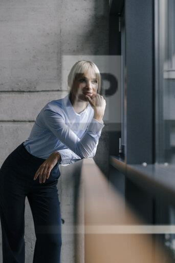 Confident businesswoman standing at window, thinking