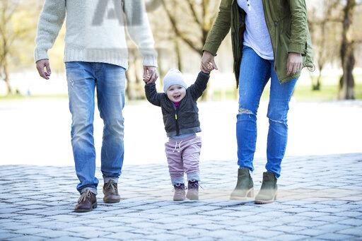 Portrait of girl walking hand in hand with parents