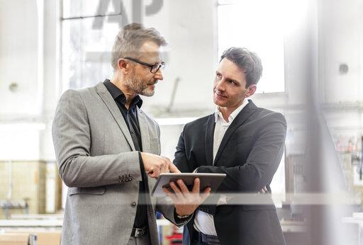Two businessmen with tablet discussing in a factory