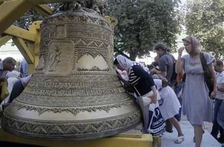 Ukrainian people kiss the new bell and pray near it, before it is lifted into place, set in the main bell tower of the golden domed Orthodox Monastery of Caves in Kiev, Ukraine, Tuesday, Aug. 19, 2014. The bell weighs 7,150 kilograms and is decorated with a unique decor, made in Ukraine. (AP Photo/Efrem Lukatsky)