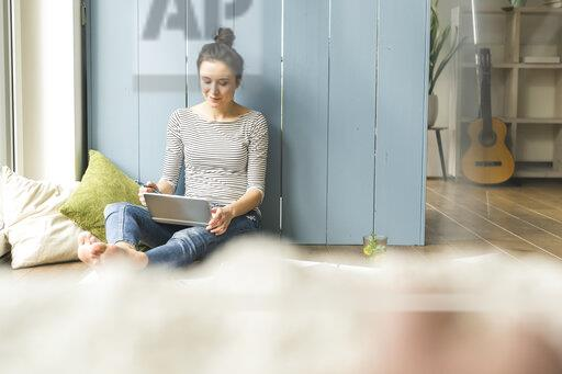 Woman sitting at the window at home working with laptop