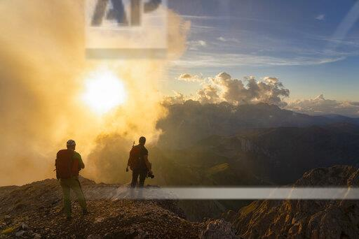 Italy, Veneto, Dolomites, Alta Via Bepi Zac, mountaineers standing in mountainscape at sunset
