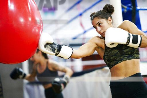 Female boxers training at punch bag in gym