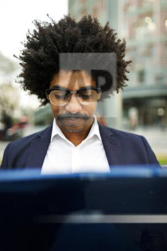 Spain, Barcelona, portrait of businessman in the city using laptop