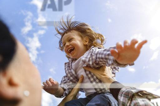 Mother lifting up happy toddler son outdoors