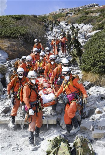 In this Sunday, Sept. 28, 2014 photo released by Tokyo Fire Department, firefighters carry an injured by Saturday's initial eruption from the summit of Mount Ontake in central Japan. A dozen more bodies were found Wednesday, Oct. 1 near the ash-covered summit of the Japanese volcano as searches resumed amid concern of toxic gasses and another eruption. (AP Photo/Tokyo Fire Department)