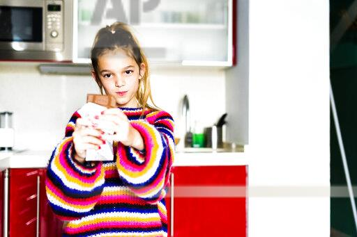 Portrait of girl in striped pullover in kitchen at home eating chocolate