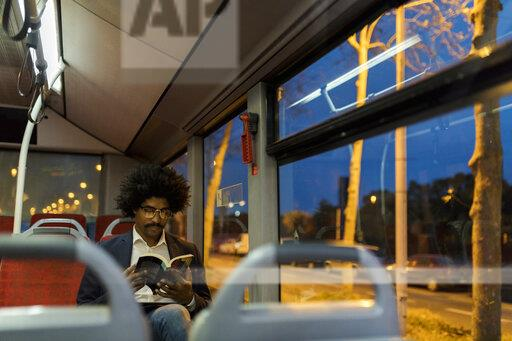 Spain, Barcelona, businessman in a tram at night reading a book