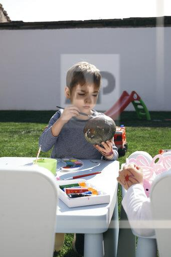 Boy painting Easter egg in garden