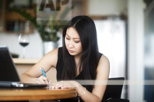 Young woman in black dress using laptop and taking notes on table at home
