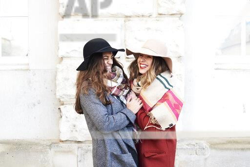 Two happy playful women wearing floppy hats