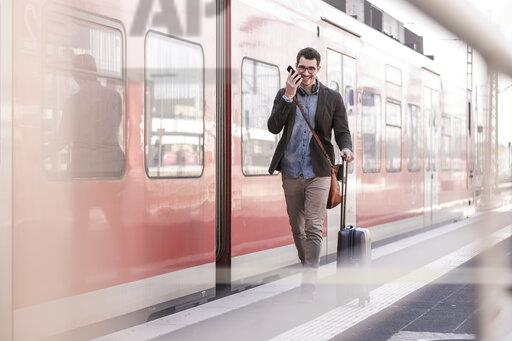 Happy young man with cell phone walking on station platform along commuter train