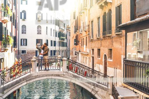 Italy, Venice, young couple standing on a small bridge taking a selfie