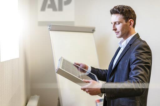 Businessman holding solar cell in office