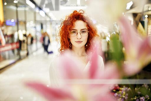 Portrait of redheaded woman behind blossom in a shopping arcade