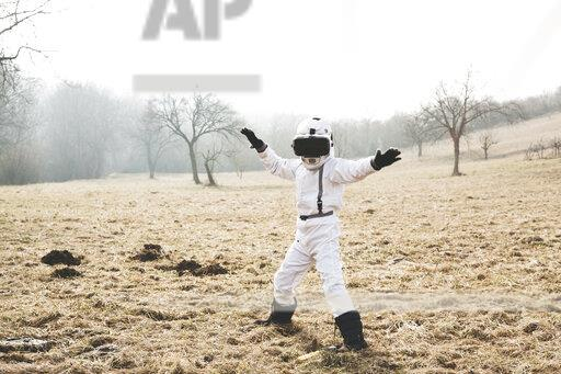 Boy wearing white space suit is posing outdoor on a meadow with virtual reality glasses