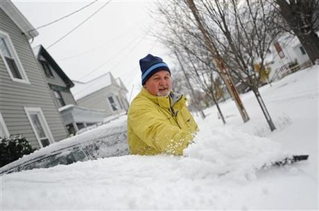 In a Tuesday, Nov. 18, 2014 photo, Brian F. Miller clears snow off his wife's car on Boyd Street in Watertown, N.Y. Before he finished his wife announced from the porch that she didn't have to go to work at the Jefferson County Courthouse due to weather.