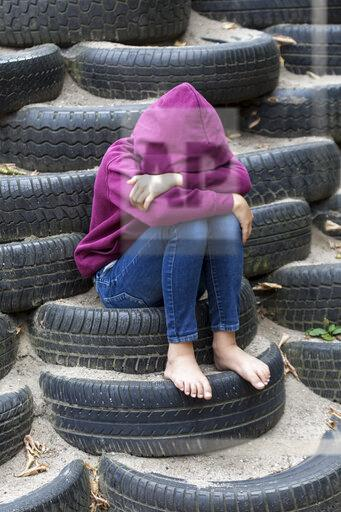 Sad girl sitting alone on playground covering her face