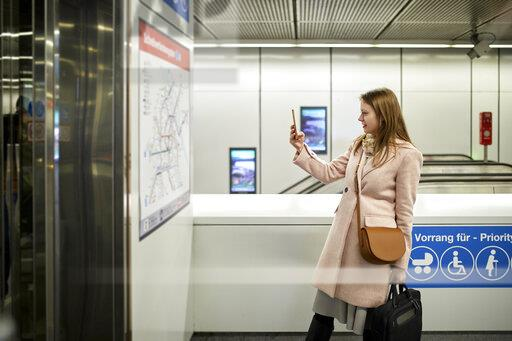 Austria, Vienna, young woman taking photo of map at underground station