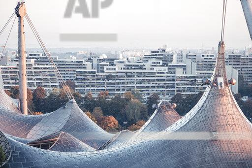 Germany, Munich, Olympic Park, Olympic Stadium, tent roof construction in the morning light, student dorms in the background