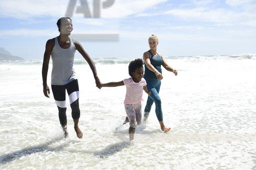 Mother with daughter and friend having fun in surf on the beach