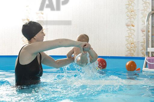 Baby swimming, mother with daughter in swimming pool