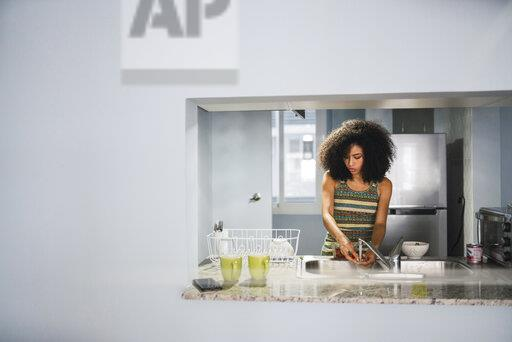 Young woman at sink in her modern kitchen