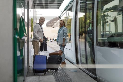 Spain, Barcelona, senior couple with baggage at tram stop in the city