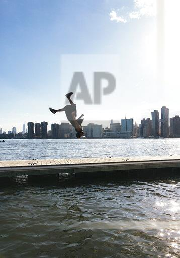USA, New York, Brooklyn, young man doing backflip on pier in front of Manhattan skyline