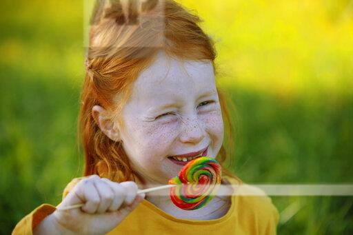 Portrait of happy girl eating a lollipop