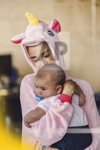 Young mother wearing unicorn onesie, standing in office, holding her son in her arms