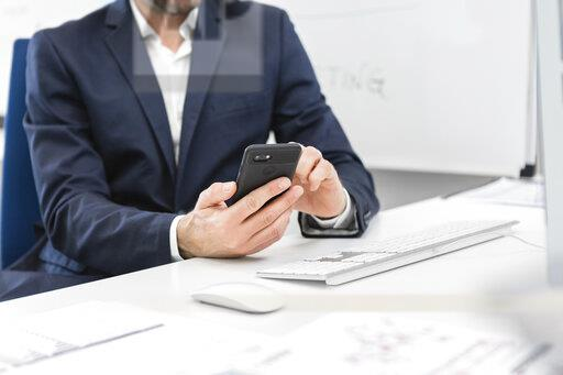 Close-up of businessman sitting at desk in office using cell phone
