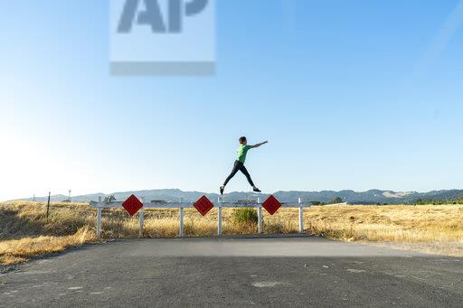 Acrobat balancing on barrier