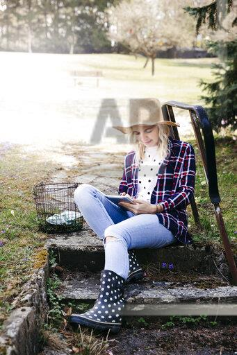 Young woman with straw hat working outdoor with her tablet