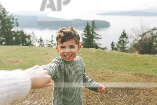 Boy holding mother's hand outdoors