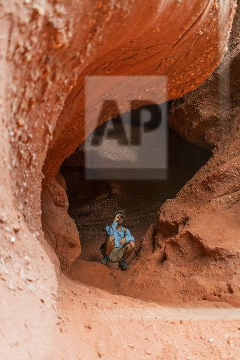 Young man sitting in a cave, looking through binoculars
