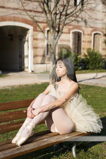 Italy, Verona, ballerina sitting on bench in the city