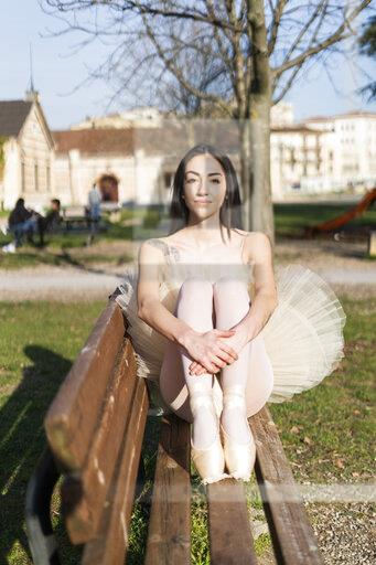 Italy, Verona, portrait of ballerina sitting on bench in the city