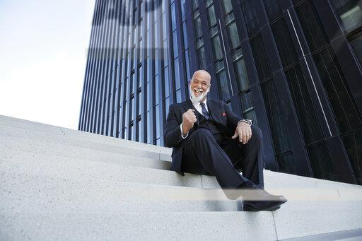 Elegant businessman, sitting on stairs in the city, enjoying his success