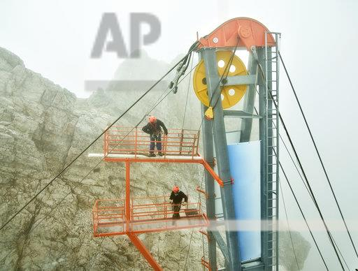 Germany, Bavaria, Garmisch-Partenkirchen, Zugspitze, installers working with rope pulley on goods cable lift