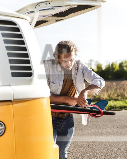 Young man on road trip with his camper, fixing surfboard on the road