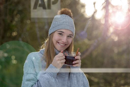 Portrait of smiling young woman with cup of tea in the woods