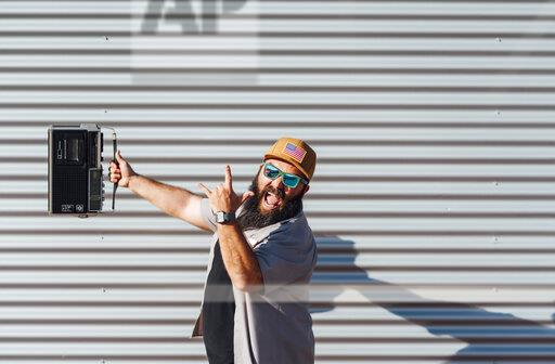 Portrait of bearded man with portable radio screaming and showing Rock And Roll Sign