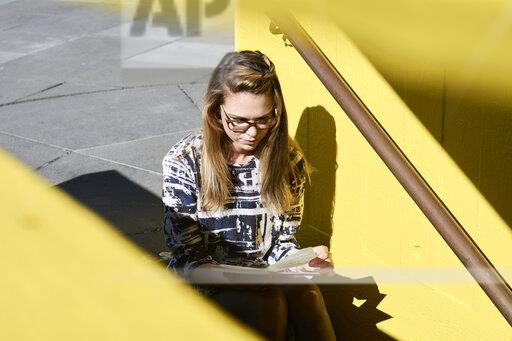 Blond student sitting on stairs outdoors looking at notebook