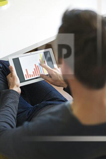 Businessman analyzing bar chart on tablet in office